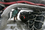 Jack Smith (cq) a truck driver for Manweiler Transport in Pueblo,CO. puts chains on his big rig...