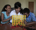 Meron Fitsum (cq), center, plays Connect Four, with her sister Makda Fitsum (cq), left, and...
