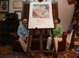Bud and Gretchen Weidknecht sit next to a limited edition Salvador Dalí lithograph signed in...