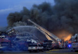 DM1307  Denver firefighters spray down a burning pile of debris at All Recycle in Denver, Colo....