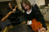 MJM103  Adele Vrooman (cq), 15, right, polishes a violin that she is constructing in Joel Noble's...