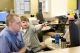 Rocky Mountain News employee Eric Brown explains stories from yesterdays paper to his son Jack,...