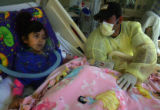 Gustavo Puga sits by the bed of his daughter Noelia Puga, 4, in intensive care at Children's...