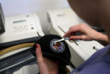 (PG1069) Raegan Corsentino works on an emblem order at Dress Code, the family's uniform store in...