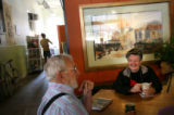 (PG1253)  Darlene Luckett (right) and John Kasman (center) have coffee at the Pour House in...