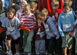 Dozens of kids make the dash for the start of the one mile run at the 26th Annual Cherry Creek...
