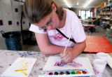 Andi Broadrick, 11, uses watercolor to paint a moon moth during open studio time, and Oasis...