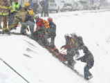 Rescue workers remove a third person from a Nissan Pathfinder which plunged some 200 feet off I-70...