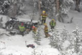 Rescue workers at the scene where a Nissan Pathfinder plunged some 200 feet off I-70 a mile west...