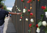 (166) A passerby reaches out to touch the roses affixed to the wall surrounding the Pepsi Center...