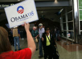 Obama volunteer Barbara Myers (cq) holds a sign to wave down incoming Obama campaign workers as...