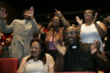 Mary McNeil-Jones and Pastor Dr. Calvin L. Kelly (both cq'd), in the front row, applaud as Richard...