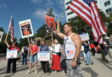Mike Jones of Denver holds a flag during a support the troops rally sponsored by Vets for Freedom...