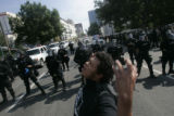 Esteban Perez, (cq) 15, of Denver, leads a chant as law enforcement officers in riot gear look on...