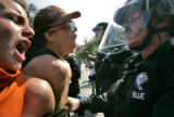 Protesters scream and confront law enforcement officers during an activist rally that marched...