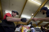 Andrew Shriver,(cq) of Denver, pays Matt Delmonico( cq), an employee at Argonaut Liquors near...