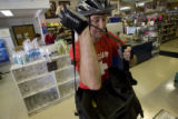 Andrew Shriver,(cq) of Denver, packs his bag before riding his bike home after shopping at...