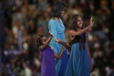 Michelle Obama and her children Sasha, left and Malia say hi to their father, Barack Obama who was...