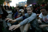 Sarah Burg, 27, of Denver, right, leans and Beth Medanich, 25, of Denver, left, sit in a circle as...