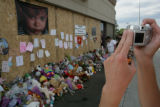 Heidi Farmer, 21, (cq) of Aurora takes a photo at a memorial of stuffed animals in remembrance of...