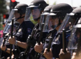 Paul Conrad photo Anti-riot police form a defensive line against a growing crowd of aggresive...