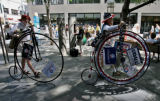 Steve Stevens (cq) and friend Lionel Ferris (cq), right to left, walk their unicycle Wednesday...