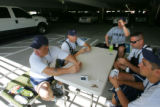 "Members of the Colorado National Guard play the cardgame, ""Hearts,"" in a parking garage..."
