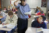 Pomona High School math teacher Jeremy Lustik (cq, center) looks over an in-class assignment of...