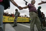 Ted Auerbach from NY holds hands with other protester as they reach the 'freedom cage' in Denver,...