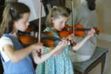 The two youngest of the Johnson family, Bethany, 9, left, and Christina, 7, play the violin as...