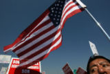 Arturo Bernal (cq), a legal immigrant originally from Mexico City, carries an American flag as he...