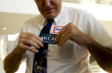 Andy Mckean, of Aurora, puts on a John McCain support sticker while attending the GOP fundraiser...