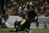 #92 Jason Brace (cq) of Colorado brings down #15 Billy Farris (cq) of Colorado State during the...