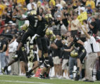 #1 Josh Smith (cq) of Colorado jumps up to celebrate with #7 Cody Hawkins (cq) after Smith ran...