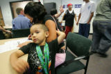 Imanol Beltran, 4, clings to his mom, Leticia Jaquez, of Denver, as she fills out forms at the...