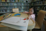 Jeslyn Zheng, 1, of Denver, looks at books in the children's section at the Schlessman Family...