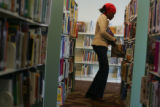 Diamond Peters, (cq) 12, of Denver, picks out books for a school project at the Schlessman Family...