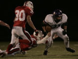 Douglas County running back, Andy Muns, right, slips past Chaparral defenders, Steve Cruz, left,...