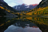 A streak of sun hits to tops of the Maroon Bells just before the rain came Tuesday morning...