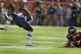 New England's Amos Zereoue, left, gets tripped up in the first quarter of play as Denver's Darrent...
