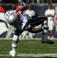Denver Broncos Darrent Williams, not shown, trips  New England Patriots Amos Zereoue in the first...