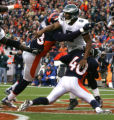 Denver Broncos Courtney Brown, left, and Curome Cox hit  Philadelphia Eagles Donovan Mcnabb as he...