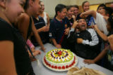 Members of Grupo Folklorico Infantil present a cake to troupe director Ramiro Loera (cq) in honor...