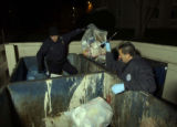 Aurora Police officers Mike Dziurgot (cq) left, and Joe Bumberger (cq) look through a dumpster at...