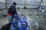 (FOREGROUND) Jacob Jaramillo (CQ), of Denver prepares his cot at the temporary homeless shelter...