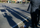 Shadows of people waving signs to drivers in rush-hour traffic are cast on University Blvd. at the...