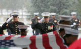 Members of the military salute as the flag is lifted off the casket of Lance Corporal Jeremy...