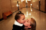 Alyssa Medina, cq, 10, kisses her adopted sister Giselle Medina, cq, shortly before a court...