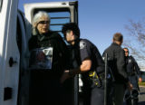 Lakewood police officer M. Munger, right, (her tag), escorts Carolyn Bninski (cq), of Boulder,...
