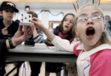 Kaymie Bullock, (cq) right, 11, reacts to a card trick by magician Lawrence Crowley (cq) at a...